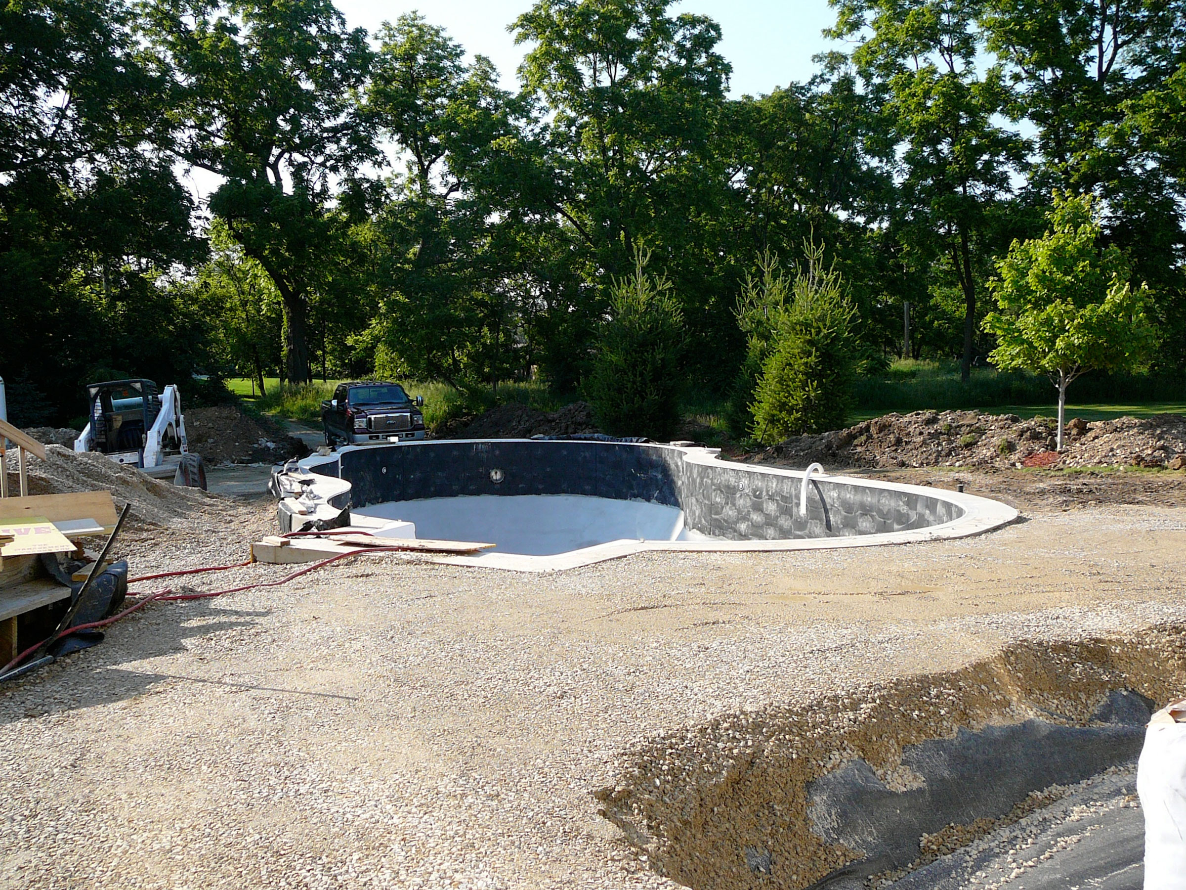 Wider view of the pool area under construction, with beginning of hot tub excavation