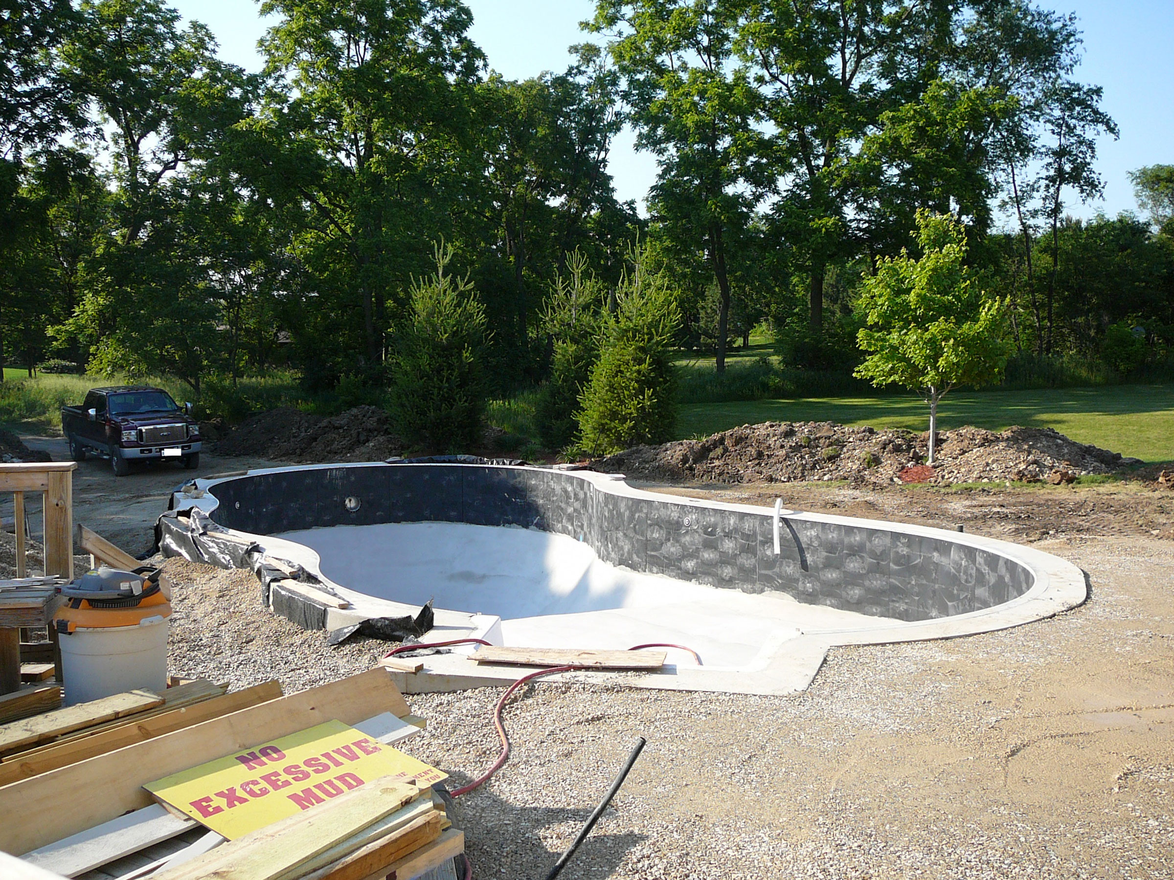 the pool is installed and hardscape excavation begins; trees are planted to provide an intimate and private space