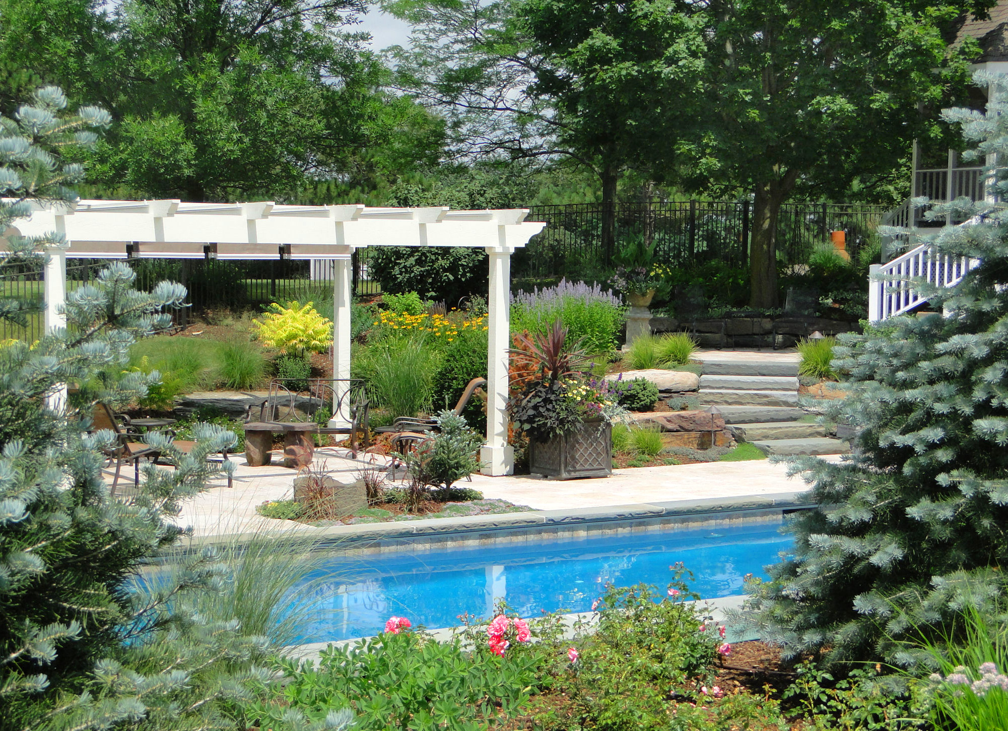 Landscaping around the pool is complete and a custom pergola has been installed