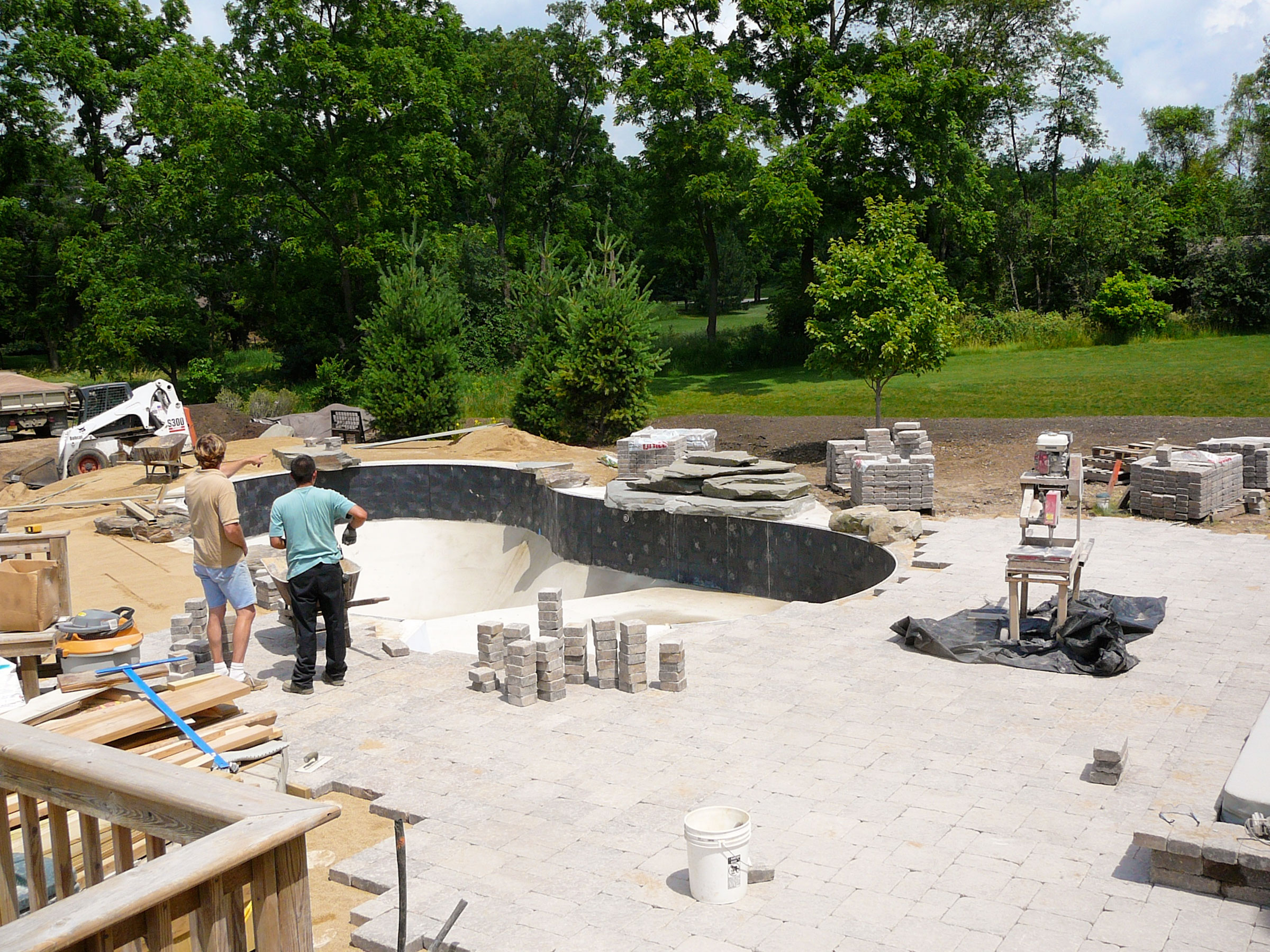 Expert patio installation using Stonehenge (Unilock) Paver Stone, and bluestone cutcropping installed for waterfall and diving rock