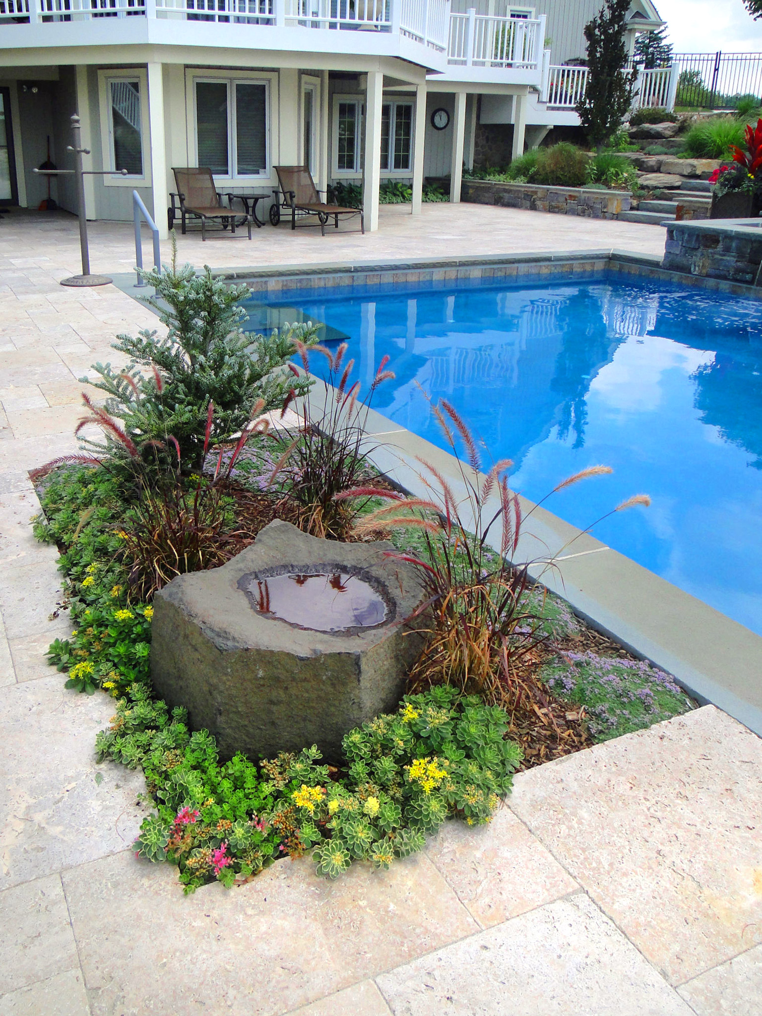 Vintage travertine pavers and full range thermal bluestone coping on this poolside are enhanced by a small garden display