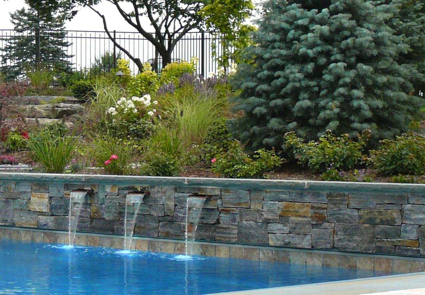 Enjoy the soothing sounds of rushing water while relaxing by the pool.