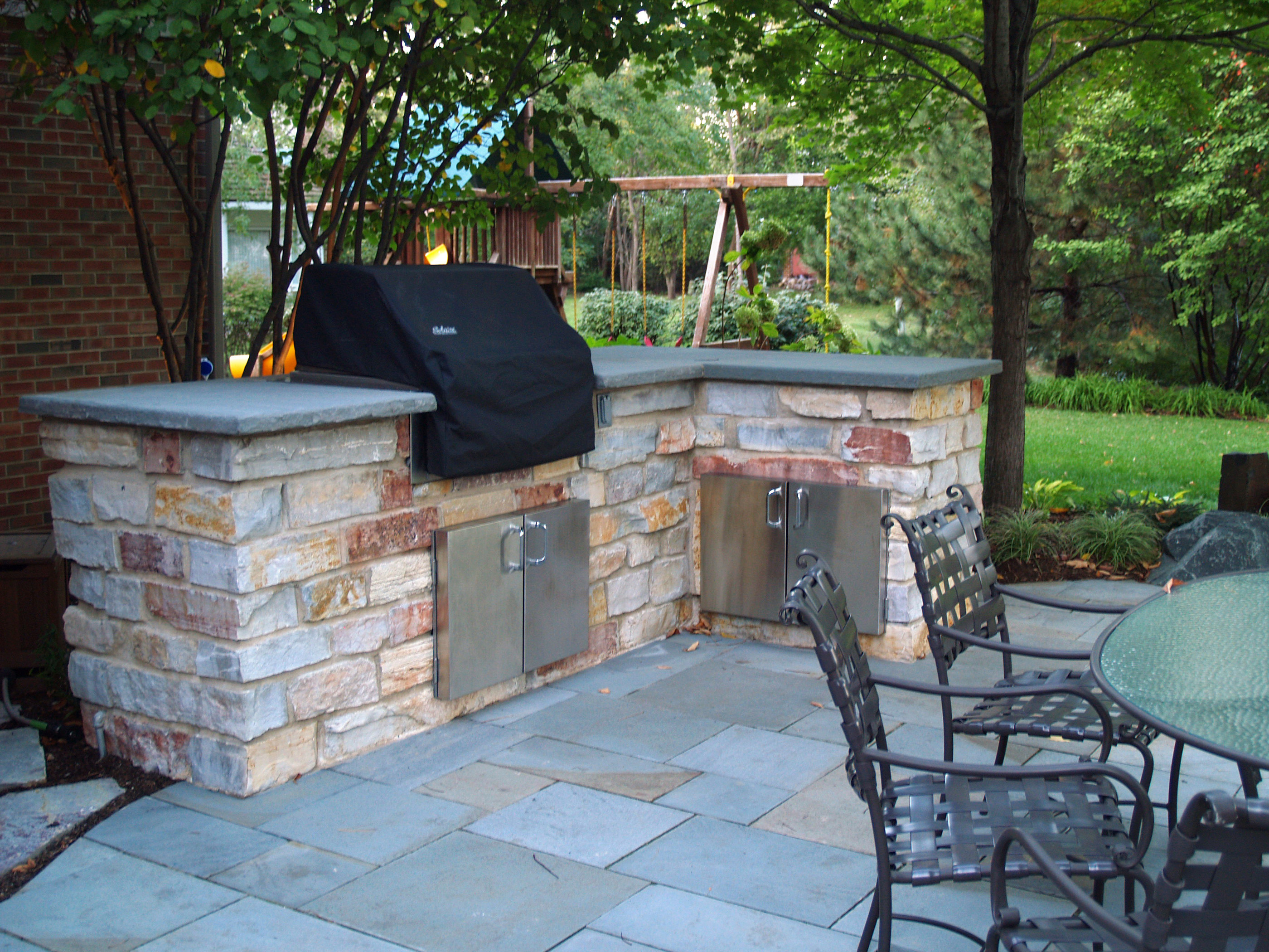 This outdoor BBQ grill and cooking area is constructed of chilton stone and finished with a bluestone top.
