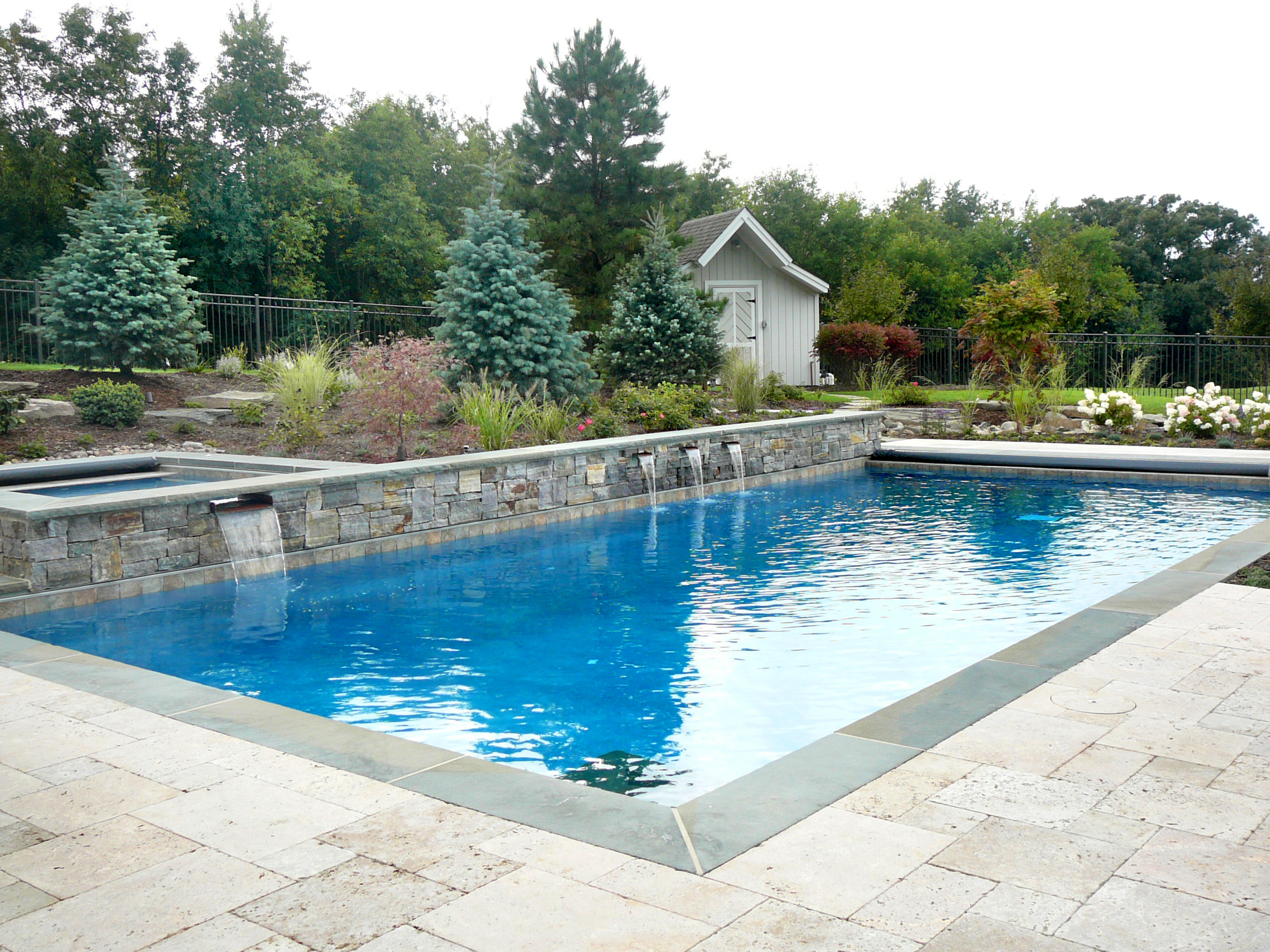 A combination of natural vintage travertine paver stone patio and full range thermal blue stone lining edge of pool, and an American granite veneer wall encasing 4 waterfalls
