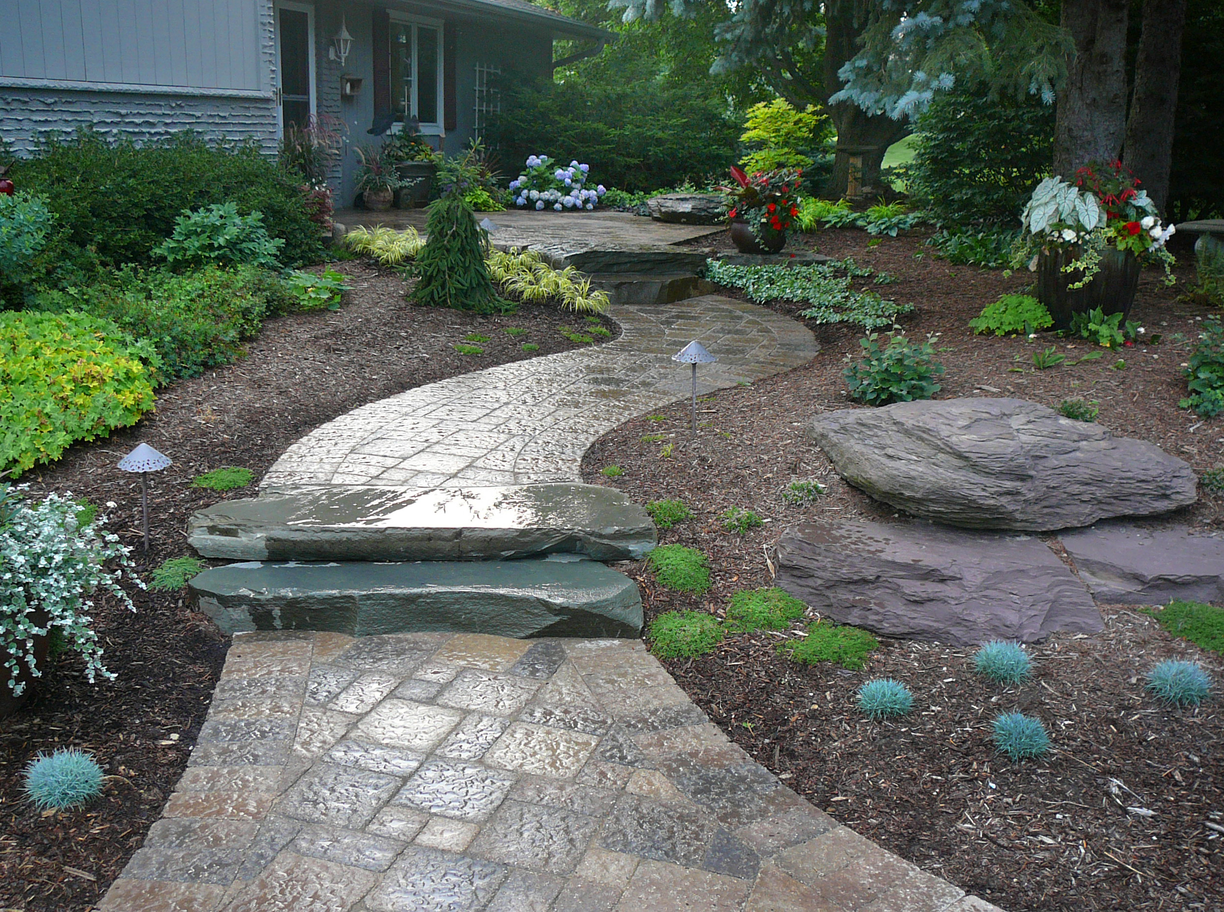 Combination of natural stone and paver stone brings a unique charm to this walkway.