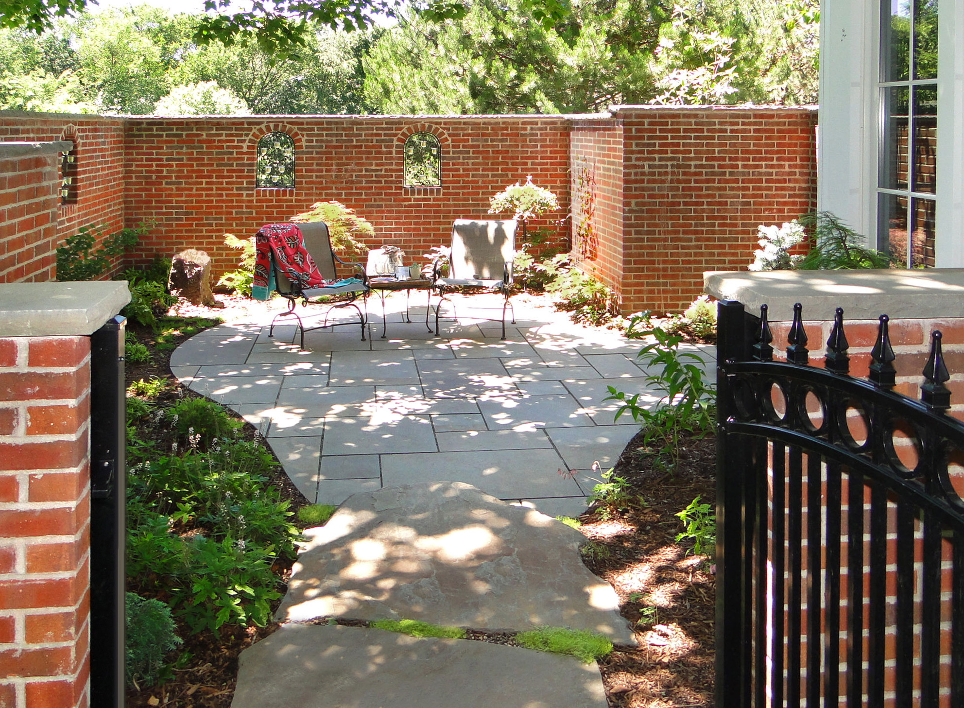Walled garden with patio hardscaping and landscaping.