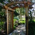A custom built cedar pergola is an inviting entry to the garden path.