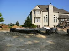 Before photo of backyard under construction; pool and hot tub installation contracted separately